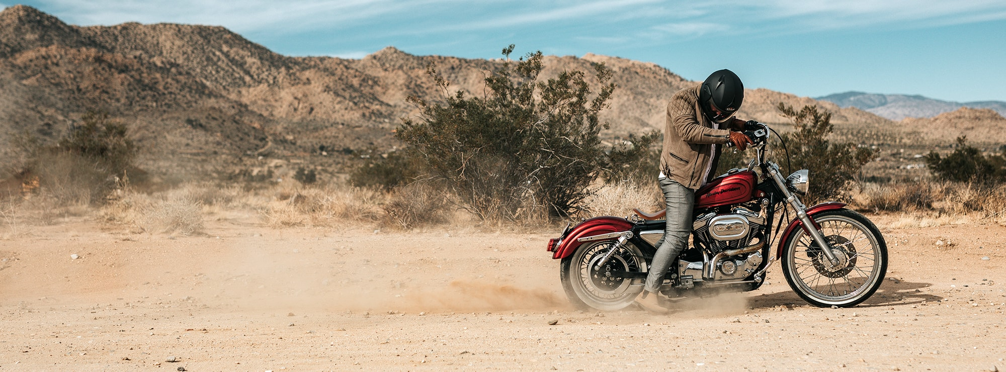 Man on Harley Davidson motorcycle in desert