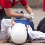 First aid is being provided to a construction worker after a workplace injury.